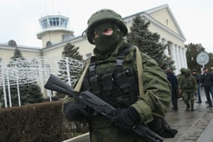 Soldiers, who were wearing no identifying insignia and declined to say whether they were Russian or Ukrainian, patrol outside the Simferopol International Airport after a pro-Russian crowd had gathered on February 28, 2014 near Simferopol, Ukraine.