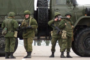 """Unidentified soldiers block a road to Ukrainian military airport Belbek not far from Sevastopol on February 28, 2014. Ukraine accused Russia of staging an """"armed invasion"""" of Crimea on Friday and appealed to the West to guarantee its territorial integrity after pro-Moscow gunmen took control of the peninsula's main airport."""