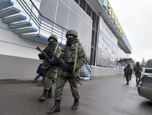 """Unidentified armed men patrol outside of the Simferopol airport on February 28, 2014. Ukraine accused today Russia of staging an """"armed invasion"""" of Crimea and appealed to the West to guarantee its territorial integrity after pro-Moscow gunmen took control of the peninsula's main airport."""
