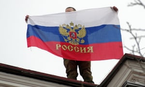 A Pro-Russian activist holds a Russian flag as he stands on the roof of Sevastopol City Hall building.