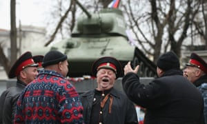 Cossacks share a laugh next to a war monument in Simferopol.