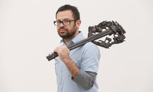 Artist Pedro Reyes holds one of his musical instruments sculpted from recycled guns