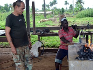 German blacksmith Manfred Zbrzezny (L) looks at one of his apprentice working  in a workshop on the outskirts of the Liberian capital Monrovia