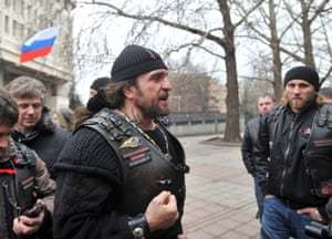 """Alexander Zaldostanov (C), nicknamed """"the Surgeon"""", leader of a group of Russian bikers called the Night Wolves, attends a rally of pro-Russian activists waving the Russian flag, in front of the local parliament building on February 28, 2014 in Simferopol, Crimea."""