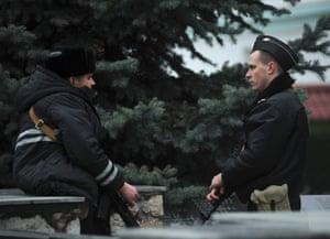 Russian, right, and Ukrainian navy sailors are deployed outside a Ukrainian Coast Guard base in Balaklava near Sevastopol, Crimea, Ukraine, Friday, Feb. 28, 2014.