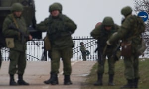 Unidentified gunmen wearing camouflage uniforms guard the entrance to the military airport at the Black Sea port of Sevastopol in Crimea, Ukraine, Friday, Feb. 28, 2014.