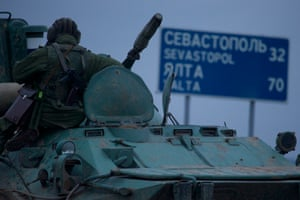 """A soldier rests atop a Russian armored personnel carriers with a road sign reading """"Sevastopol - 32 kilometers, Yalta - 70 kilometers"""", near the town of Bakhchisarai, Ukraine, Friday, Feb. 28, 2014."""
