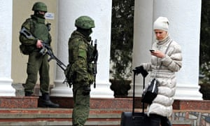Armed men patrol at the airport in Simferopol, Crimea