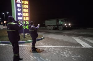 Gas station employees take pictures of a convoy of 20 Russian armoured personnel carriers and trucks full of troops pictured in the evening 3km from Simferopol of Crimea where they are reportedly heading on February 28, 2014 near Simferopol, Crimea, Ukraine.