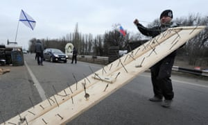 One of the  men who called themselves members of local militia carries a makeshift road spike barrier to block a highway that connect Black Sea Crimea peninsula to mainland Ukraine at their checkpoint near the city of Armyansk, on February 28, 2014.