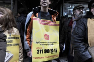 A demonstrator  holds a banner reading ' your house goes on auction? they cut your electricity or water? call the solidarity  group'  during a protest  outside a tax office in central Athens against auctions of homes , high taxes and foreclosures on February 3, 2014.
