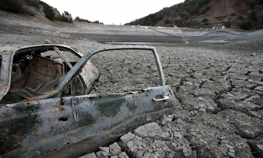 A car sits in dried and cracked earth of what was the bottom of the Almaden Reservoir in San Jose, California.