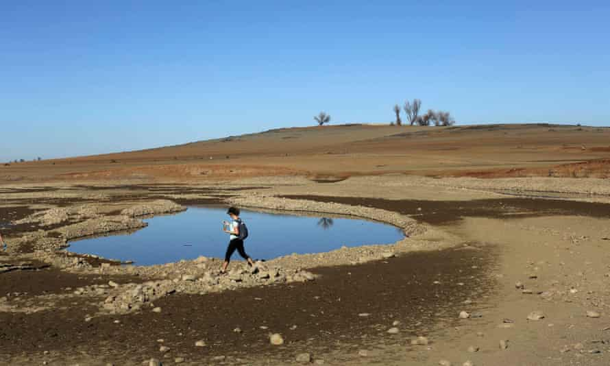 A visitor walks near the receding waters at Folsom Lake, which is 17% of its capacity, in Folsom, California