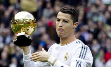Cristiano Ronaldo poses with the Golden Ball at the Santiago Bernabeu
