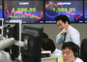 A currency trader gestures in front of screens showing the Korea Composite Stock Price Index and foreign exchange rate at the Korea Exchange Bank headquarters in Seoul, South Korea, Tuesday, Feb. 4, 2014.
