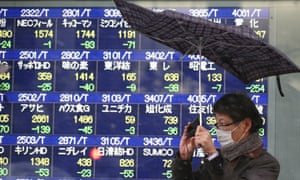 A man reacts to a gust of wind as it starts to snow in front of an electronic stock board at a securities firm in Tokyo Tuesday, Feb. 4, 2014.