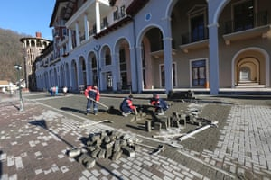 Workers work to cobble the road outside the Gorki Plaza East hotel.