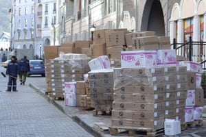 Pallet-loads of hand soap and sugar stand in the street waiting to be distributed around the Olympic village.
