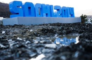 A Sochi 2014 logo standing on mud and rubble in front of snow-covered mountains is reflected in a puddle.