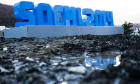 A Sochi 2014 logo standing on mud and rubble in front of snow-covered mountains is reflected in a puddle