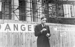 William Burroughs: Burroughs lights a cigarette outdoors in Paris, c 1964