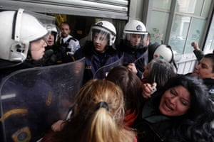 Laid-off cleaning staff of the Ministry of Finance scuffle with riot police at the entrance to the ministry in Athens, Greece, 04 February 2014. Protesters, who have been protesting against lay-offs over the past four months, claimed that they have been replaced by contractors who charge much more than they were paid.