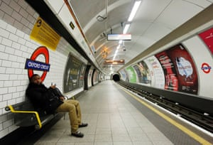 A passenger waits for a tube that did not arrive on an empty platform during rush hour at Oxford Circus.