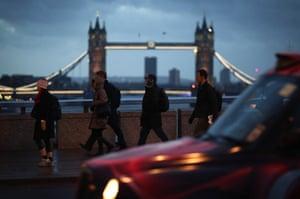 Pedestrians walk north across London Bridge.