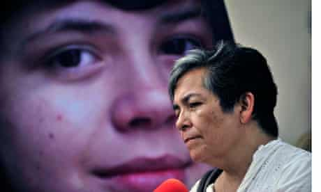 a woman protesting in front of an image of her child