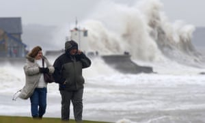 A man and woman walk along the seafront as waves break over the harbour wall at Porthcawl in Wales.