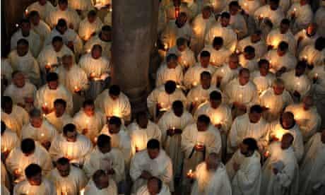 Catholic clergymen hold candles