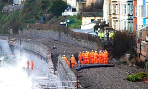 Engineers and members of the emergency services combine to survey the sunken section of the mainline railway track near the coastal town of Dawlish.
