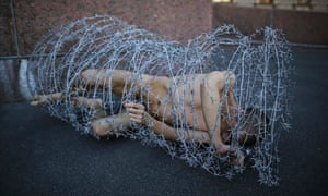 Pyotr Pavlensky lies on the ground, wrapped in barbed wire roll