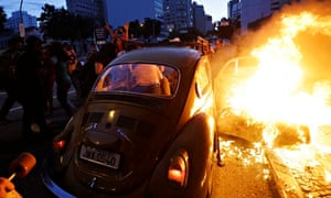 Car on fire during protests against quality of public services in Brazil