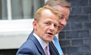 David Laws looks at the camera with Michael Gove in the background as the pair leave Downing Street