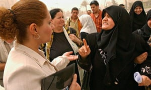 A conservative Muslim woman argues with another in western dress on a street in Baghdad
