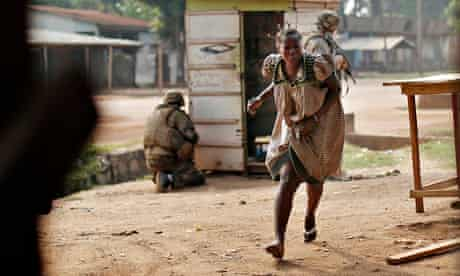 A woman runs for cover as heavy gunfire erupts in the Miskin district of Bangui