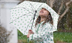 Mixed race girl with umbrella in rain