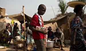 一名街头小贩走在班吉机场的难民营