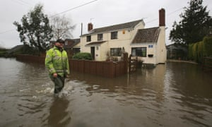 A man wades past a property that flooded this morning in Fordgate on the Somerset Levels near Bridgwater, Somerset.
