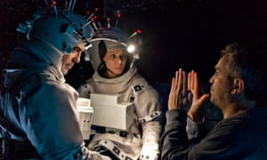 Alfonso Cuarón directs Geroge Clooney and Sandra Bullock on the set of Gravity.