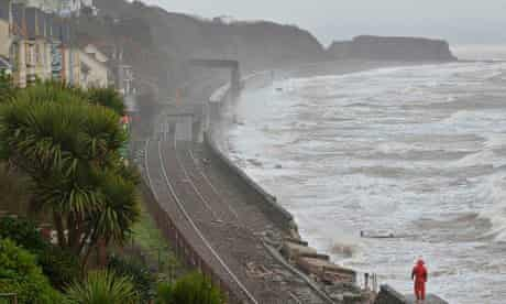 Rail workers inspect damaged track along the seafront at Dawlish