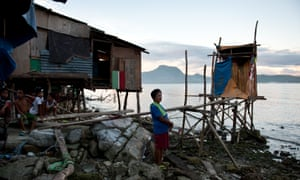 A woman, who survived the typhoon by climbing up a steep hill, stands beside her temporary home.