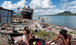 Girls wash their clothes on a stretch of coast in Tacloban where homes were flattened by the storm surge and ships crashing onto the shore.