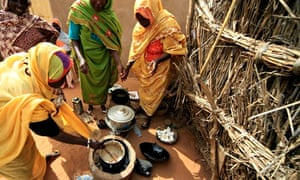 Women cook on stove made out of mud