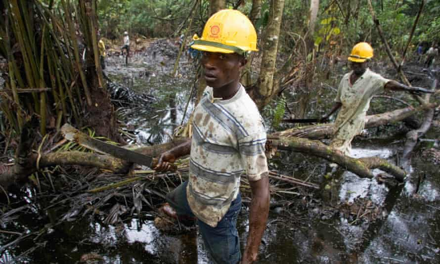 19 Jul 2004, Oloibiri Town, Nigeria. Workers subcontracted by Shell clean up an oil spill from an abandoned well.