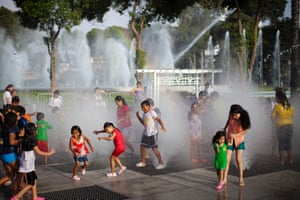 While in warmer climes, children play in a water fountain in Exposition Park in downtown Lima , Peru.