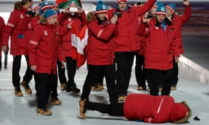 A member of Austria's delegation lies on the ground after falling during the Opening Ceremony of the Sochi Winter Olympics at the Fisht Olympic Stadium.