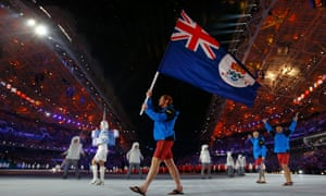 Flag-bearer Dow Travers of the Cayman Islands leads his country's delegation during the opening ceremony of the 2014 Sochi Winter Olympics.