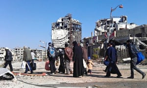 Civilians carry their belongings as they walk towards buses evacuating them from besieged Homs